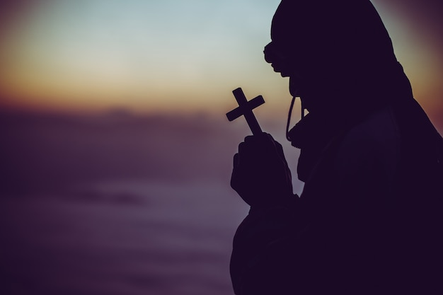 Silhouette of a man praying with a cross in hand at sunrise. Free Photo