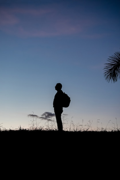 Silhouette of a man in profile with backpack in back outdoors Premium Photo