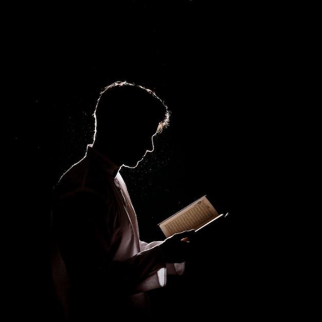 Silhouette of man reading in quran Premium Photo