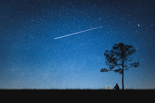 Silhouette of man sitting on mountain and night sky with shooting star. alone concept. Premium Photo
