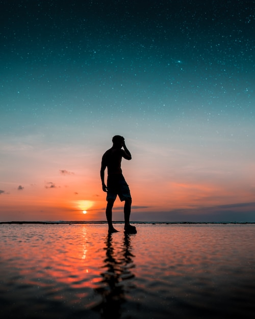 Silhouette of a man standing on the water at the beach with an amazing sunset Free Photo