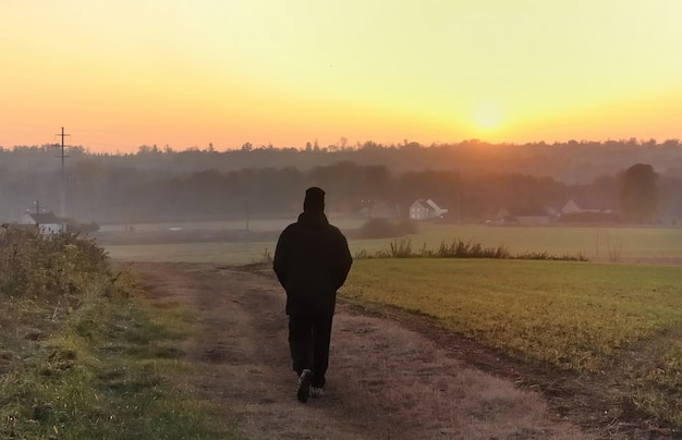 Silhouette a man walking at twilight on a path towards  to the sun setting Premium Photo