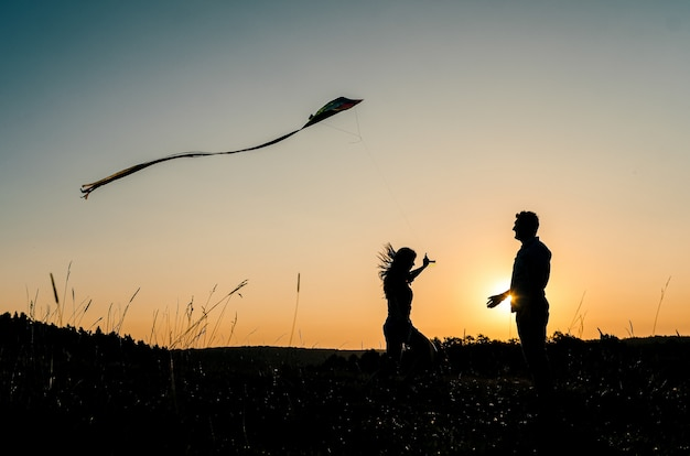 Silhouette of man and woman launching kite on nature Premium Photo