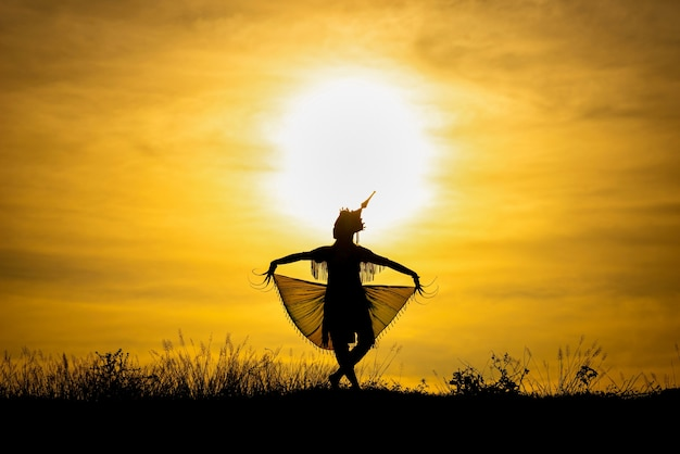 Silhouette manohra women dance with sunset in south of thailand. Premium Photo