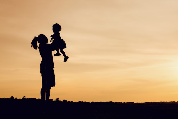 Silhouette of mother and daughter lifting child in air over scenic sunset sky at riverside. Premium Photo