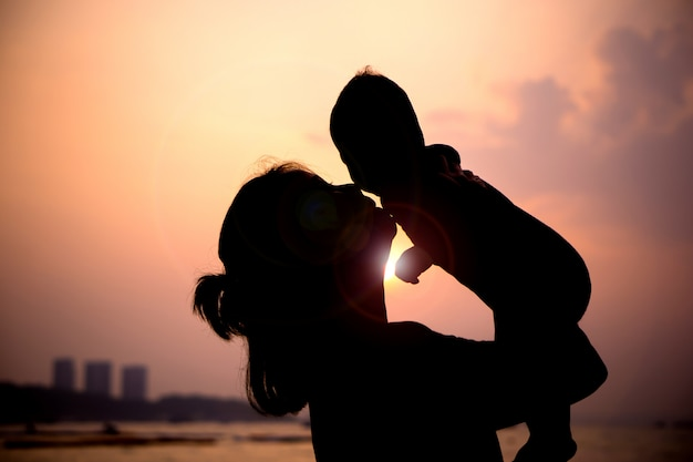 Silhouette of mother playing with her toddler at sunset Premium Photo