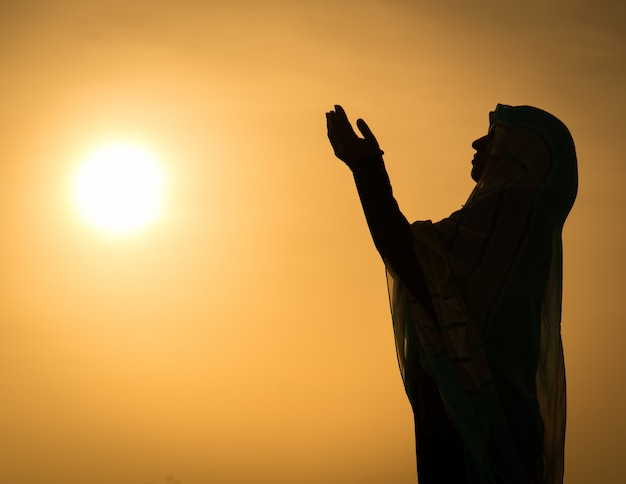 Silhouette muslim arabic woman praying with her hands up ...