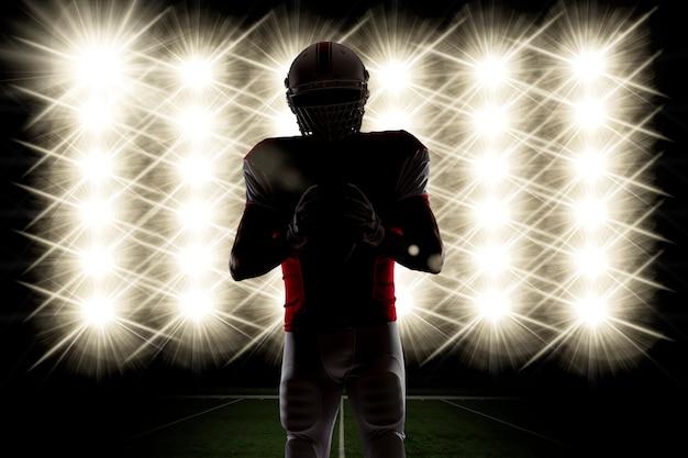 Силуэт футболиста в красной форме перед огнями. Бесплатные Фотографии