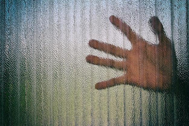 닫힌 된 유리 문을 통해 문에 손의 실루엣. 프리미엄 사진