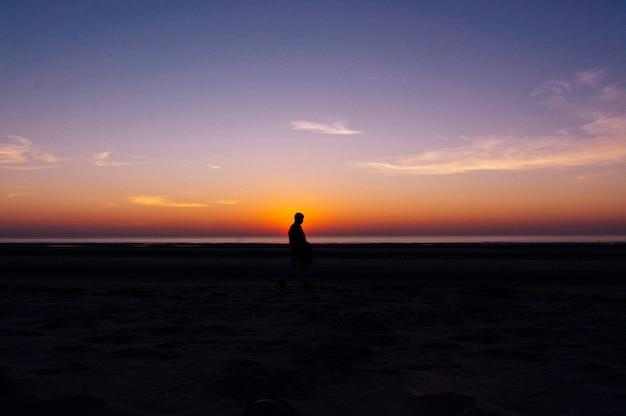 バックグラウンドで夕日の美しい景色とビーチの上を歩く孤独な人のシルエット 無料写真