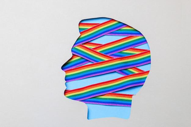 男性の頭とlgbtプライドのレインボーリボンのシルエット。頭の中でゲイ。 Premium写真
