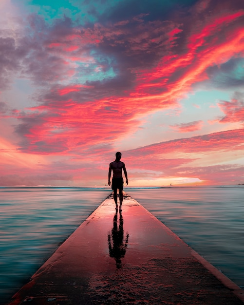 彼の反射と美しい息をのむような雲と石の桟橋を歩く男性のシルエット 無料写真