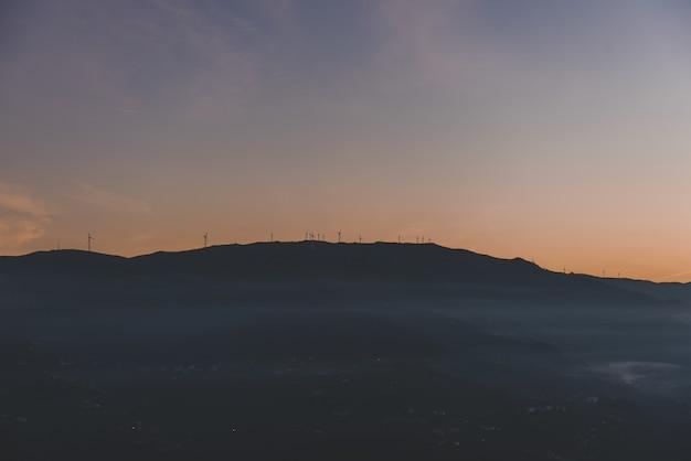 上に風車のある山のシルエット 無料写真