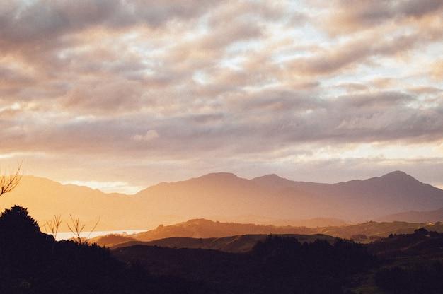 息をのむような夕焼け空の下で美しい山々の範囲のシルエット 無料写真