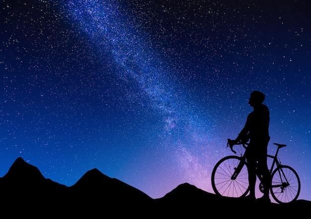 天の川に対してロードバイクのサイクリストのシルエット。星空の山のロードサイクリストの美しい夜の風景 Premium写真