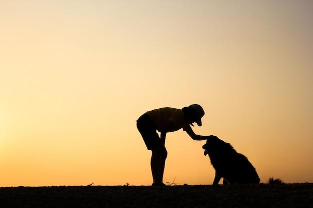 女の子と美しい夕日の背景と彼女の犬のシルエット。 Premium写真