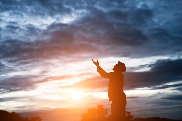기도 잘 생긴 아시아 남자의 실루엣입니다. 무료 사진