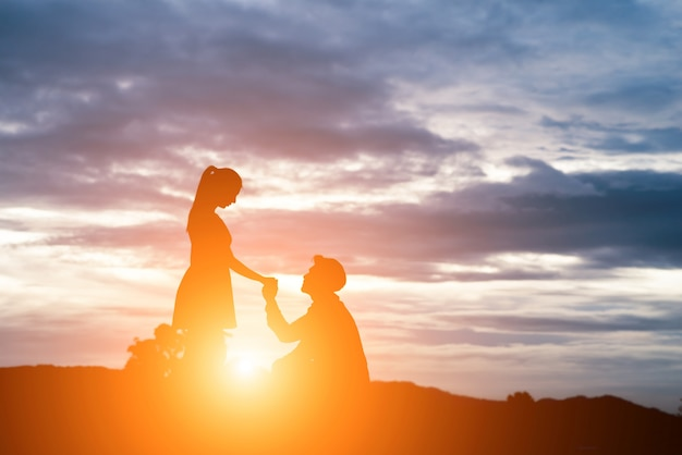 silhouette of man ask woman to marry on  mountain background. Free Photo