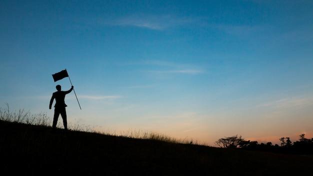 空と太陽の光の上の山の頂上に男のシルエット Premium写真