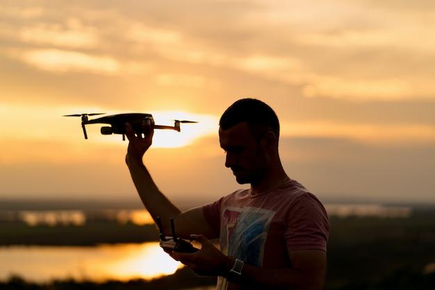 Силуэт человека пилотирования беспилотник на закате с солнечным небом в фоновом режиме Бесплатные Фотографии
