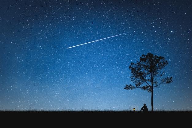 슈팅 스타와 산과 밤 하늘에 앉아 남자의 실루엣. 혼자 개념. 프리미엄 사진