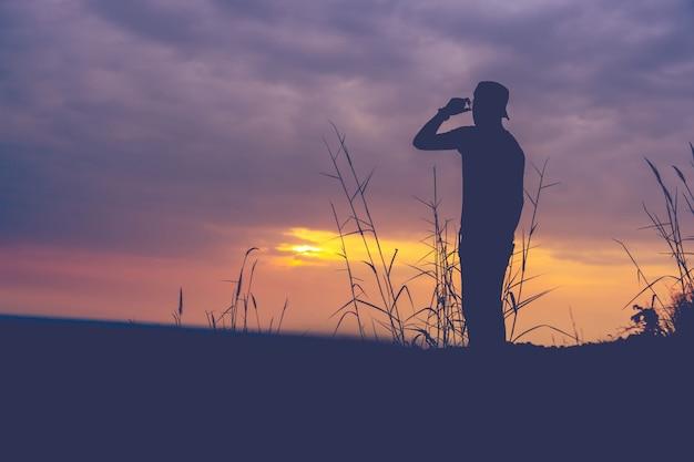 日没時に山に立っている男のシルエット Premium写真