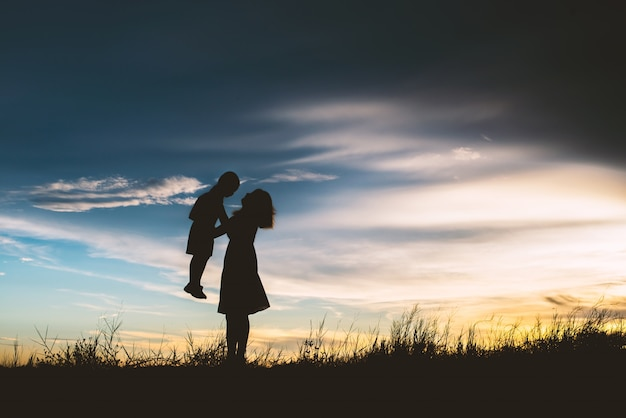 Silhouette of mother playing with her son in the meadow Free Photo