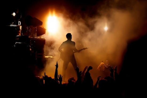 Силуэт гитариста на сцене над поклонниками. Premium Фотографии