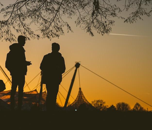 日没時にツリーの下で互いに話している2人のシルエット 無料写真
