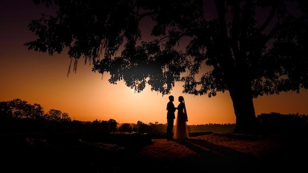 Силуэт свадьбы влюбленная пара, целующаяся и держащаяся за руку во время заката с вечерним небом Premium Фотографии
