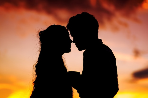 silhouette of wedding couple in love kissing and holding hands