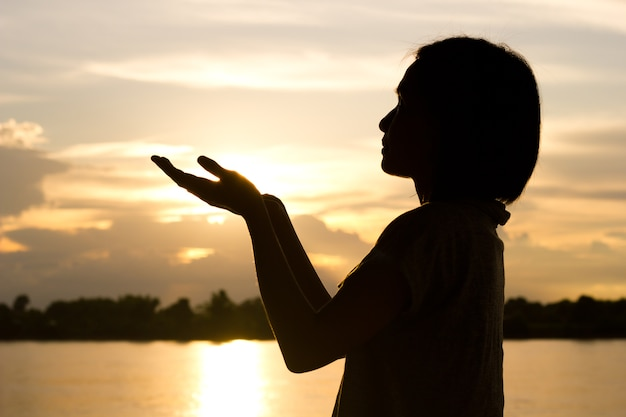Silhouette of woman praying over beautiful sunset ...