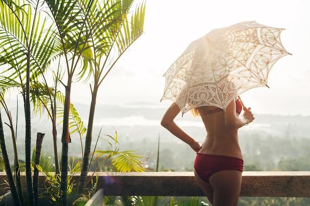 バリ、スキニーフィギュア、夏のスタイルのアクセサリーで休暇旅行の日当たりの良い熱帯の別荘リゾートでレースの太陽傘を保持している赤いビキニ水着を着ている美しいスリムな体を持つ女性のシルエット 無料写真