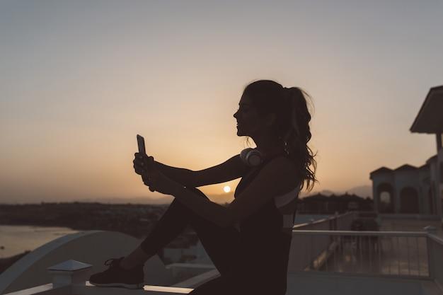 Силуэт молодой привлекательной женщины в спортивной одежде, делая селфи на берегу моря на закате. выражение позитива, активного образа жизни, радости, веселого настроения. Бесплатные Фотографии
