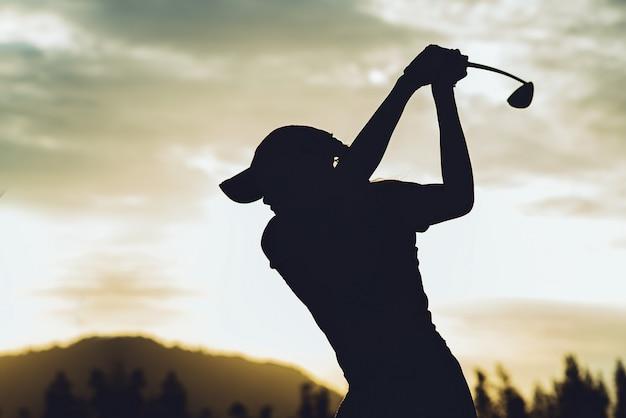 젊은 여성 골프 선수의 실루엣 청소를 명중하고 골프 스윙을하고 골프 코스를 유지, 그녀는 휴식 시간 운동을 않습니다 프리미엄 사진