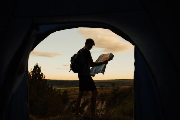 山で彼のテントの近くの地図を探索する若い観光客のシルエット。 Premium写真