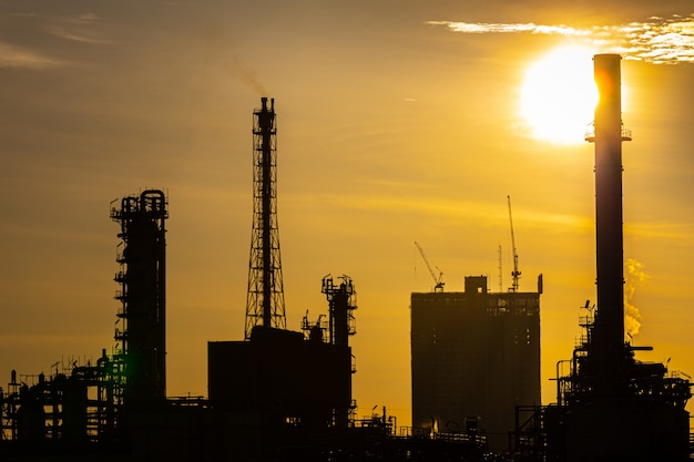 Silhouette of oil and gas refinery industry plant with glitter lighting and sunrise in the morning Premium Photo
