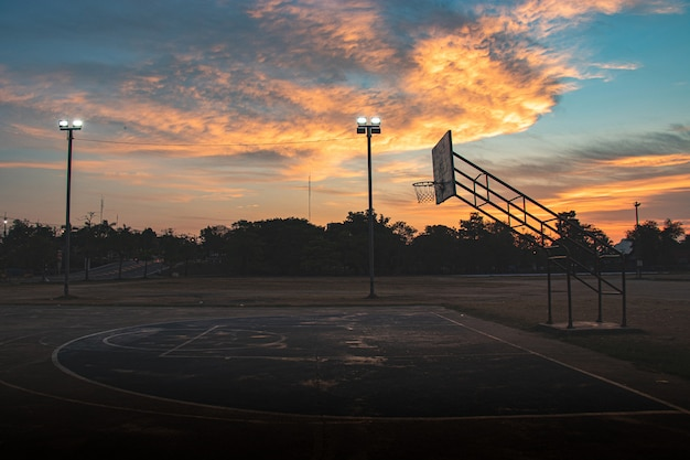 Silhouette of outdoor basketball court with dramatic sky in the sunrise morning Premium Photo
