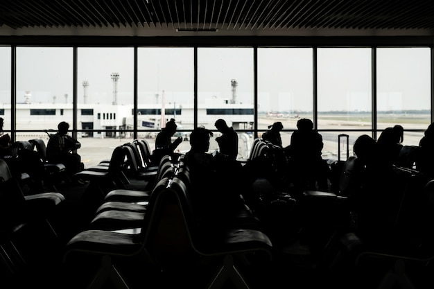 Silhouette of passangers waiting for the flight at the airport Premium Photo