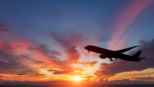 The silhouette of a passenger plane flying in sunset. Premium Photo