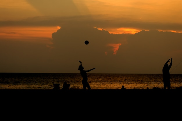 Silhouette people are playing beach volleyball. Premium Photo