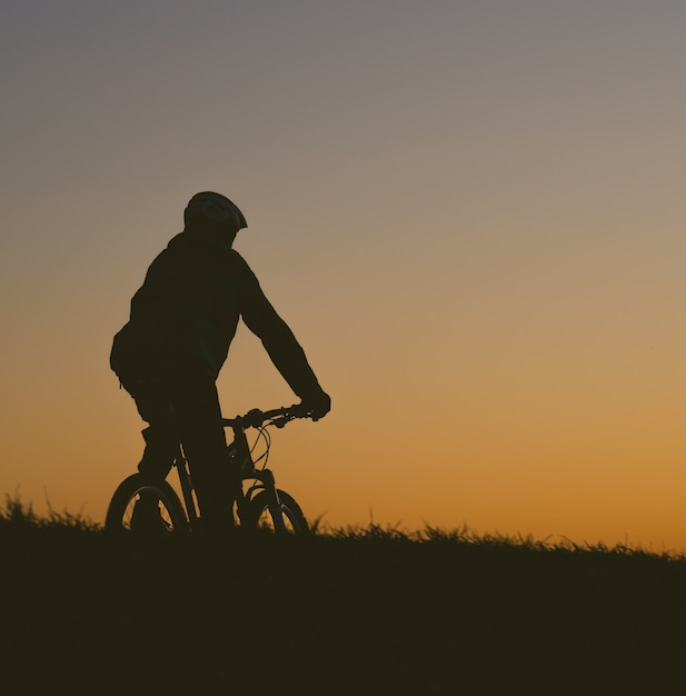 Silhouette of a person riding a bicycle on a field during a sunset Free Photo
