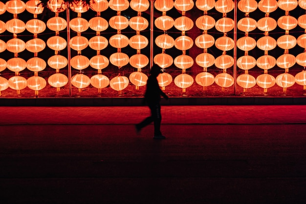 Silhouette of a person walking near the lantern lamps at ngiht in dalian, north-east china Free Photo