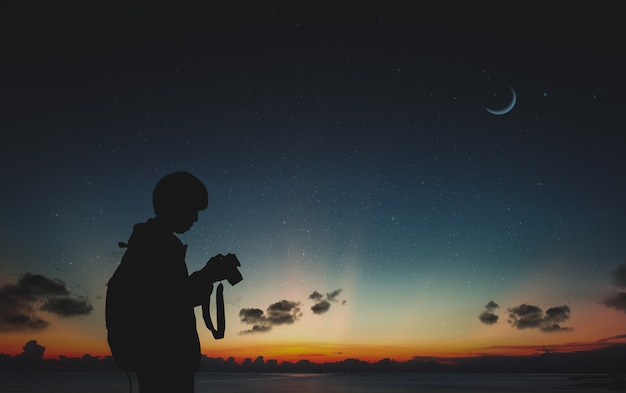 Silhouette of photographer standing in nature with moon and night sky. Premium Photo