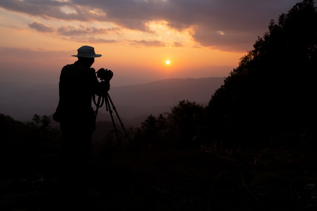 Silhouette of a photographer who shoots a sunset in the mountains Free Photo