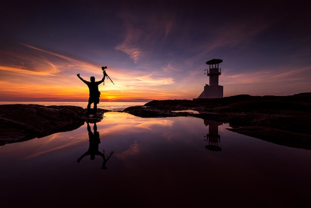 Silhouette photographer with lighthouse Premium Photo