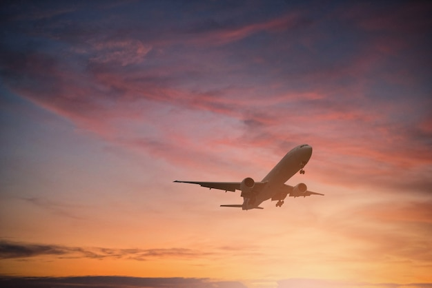 Silhouette of plane fly on sky during sunset. Premium Photo