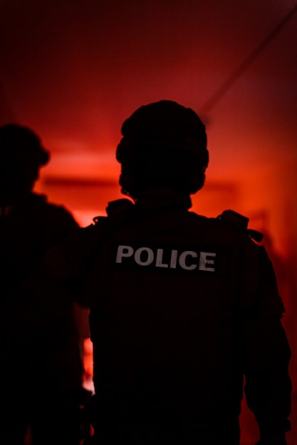 Silhouette of a police officer. police commando in action, arresting the perpetrator in the building Premium Photo