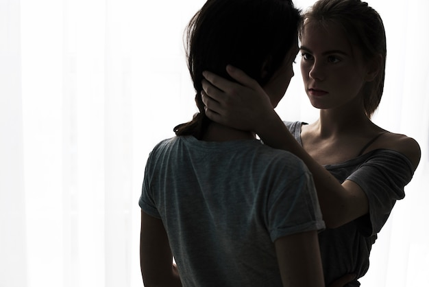 Silhouette of romantic young lesbian couple looking at each other standing against white curtain Free Photo