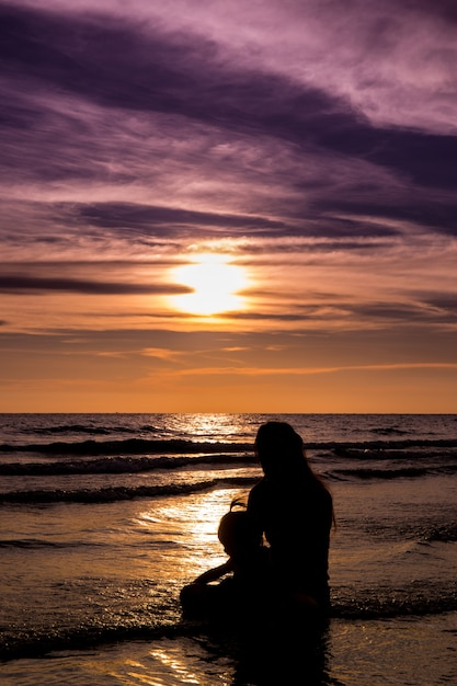 Silhouette sea mom and daughter Premium Photo